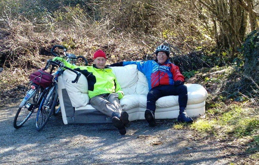 Cyclists rest on a Carmarthenshire settee.